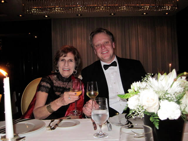 couple in formal wear toasting