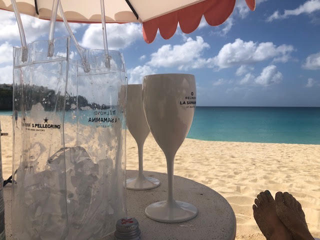 view of the beach and ocean from St Maarten St Martin with umbrella table in foreground