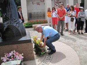 an American man lays a wreath at the base of a memorial as a way of honoring the fallen