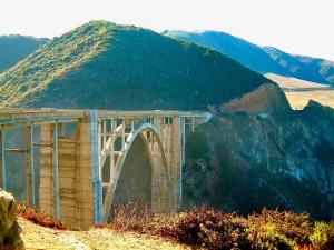 cross the Bixby Creek Bridge on your California roadtrip. Image shows Bixby Creek Bridge in the distance.