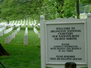 """Arlington entrance sign reminds us to honor the fallen. The sign reads """"Welcome to Arlington National Cemetary our nation's most sacred shrine. Please conduct yourselves with dignity and respect at all times. Please remember these are hallowed grounds."""""""