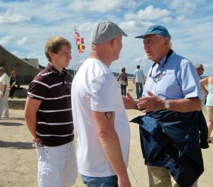 two younger men speak with an older man who served in WWII