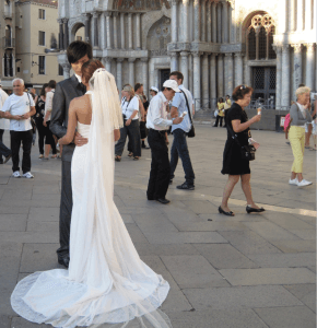 Couple in Wedding Attire in foreground as people pass by in background at St. Mark's Square in Venice
