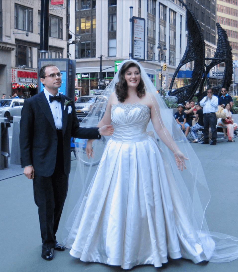 Couple in wedding attire in foreground, New York in Background