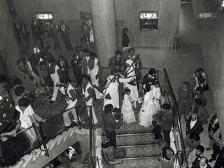 Black and white picture of wedding party on the stairs with bagpiper in background