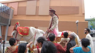 Man in turban rides a white horse guided by a group to his wedding